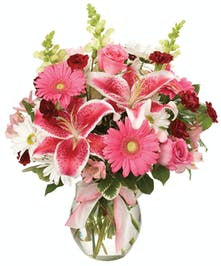 Pink, white and burgundy flowers in a clear glass vase tied with a pink ribbon.
