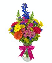 Bright, colorful blooms in a clear glass vase, available in 3 sizes.