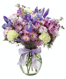 Alstromeria, iris, carnations, spray roses, daisies and other flowers in hues of blue and purple in a clear glass vase with purple ribbon.
