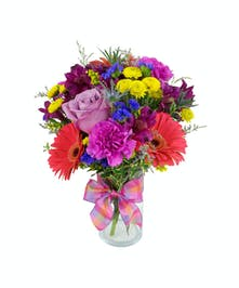 Bright and colorful flowers are arranged in a cylinder vase.
