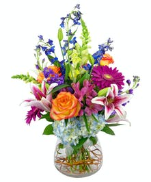 A striking variety of flowers in a clear glass vase.