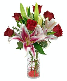 Stargazer lilies and roses are arranged in a cylinder vase with stones, wire and more.