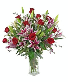 Fabulous stargazer lilies with long stemmed red roses in a clear glass vase.