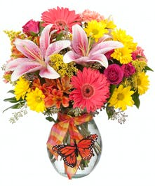 Pink, yellow and orange flowers in a clear glass vase with a Monarch butterfly decoration.