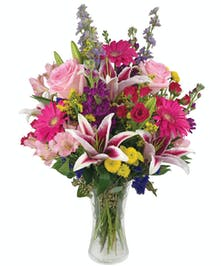 Tall and showy flowers in various colors in a glass vase.