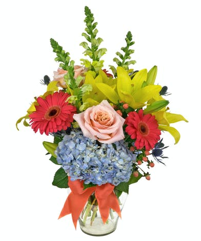 Flowers in shades of coral, peach, blue and yellow in a clear glass vase tied with a ribbon.