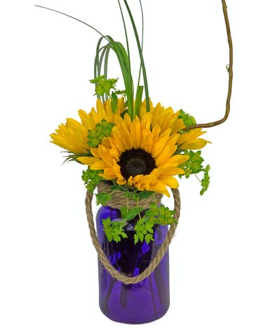 Pretty purple vase is filled with bright sunflowers and other natural looking greenery.