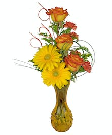 This yellow vase is filled with gorgeous flowers in yellow and orange.