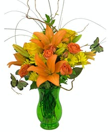 A green vase, filled with orange nad yellow flowers, curly willowand butterflies.