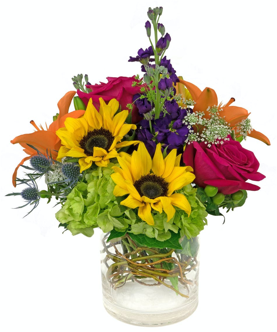 A truly gorgeous sunflower mix with so much color and texture, in a cylinder vase.