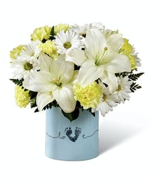 Keepsake container filled with yellow and white blossoms to celebrate baby.