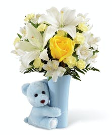 A tiny bear and small vase of flowers to celebrate the day!
