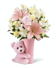 A tiny bear and small vase of pink flower to celebrate her arrival.