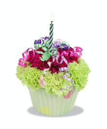 Ppolka dot cupcake container filled with carnations to look like a cupcake, topped with ribbon and a birthday candle.