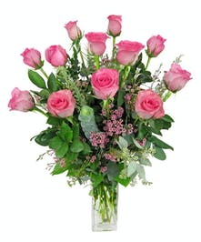 One dozen soft pink roses in a clear glass vase.