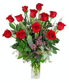 One dozen premium red roses arranged in  a clear glass vase.