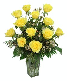 One dozen yellow roses arranged in a clear glass vase, so pretty.