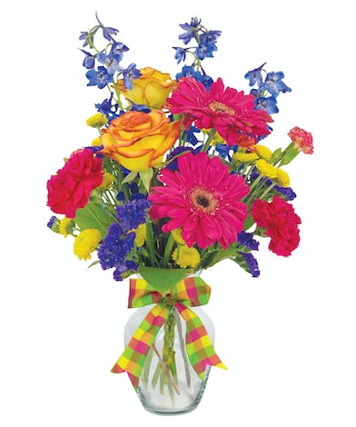 Hot pink, orange, yellow and purple gerbers, delphinium, roses and carnations in a clear glass vase tied with a plaid bow.