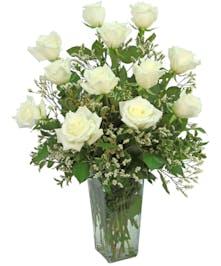 One dozen long stemmed white roses, so delightful, arranged in a clear glass vase.