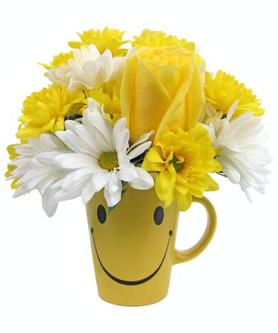 Yellow smiley face mug filled with yellow roses and white and yellow daisies.