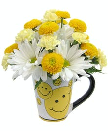 White ceramic mug with smiley faces on it, filled with yellow and white flowers.