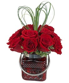 One dozen red roses in a red cut glass cube with handle, and heart-shaped greenery above.