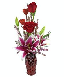 A lovely creation featuring roses and lilies.