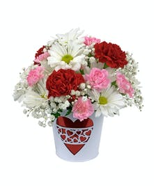 Red, white and pink carnations, mini carnations, daisies and babies breath arranged in a red and white tin vase with heart on the front.