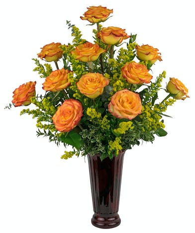 A tall, flared, red vase filled with bi-color yellow & red roses, that open beautifully.