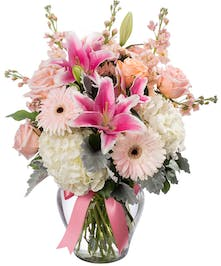 Bouquet of white hydrangea, gerbera daisies, pink roses, peach stock, and stargazer lilies in a clear glass vase tied with a pink bow