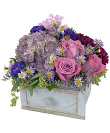 Various flowers in shades of purple are artfully displayed  in this rustic, wooden drawer.
