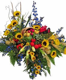 Bold colored flowers and vegetables arranged in a casket spray.