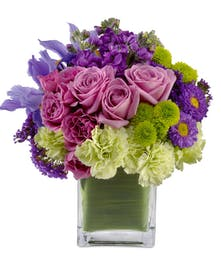 Lavender roses, green carnations and other flowers in a green glass cube vase.