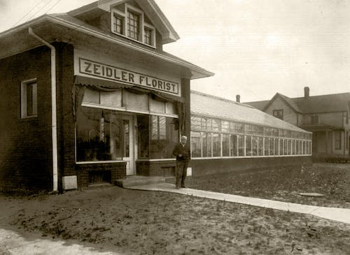 Karl Zeidler stands outside the floral shop and greenhouse that bears his name, circa 1900